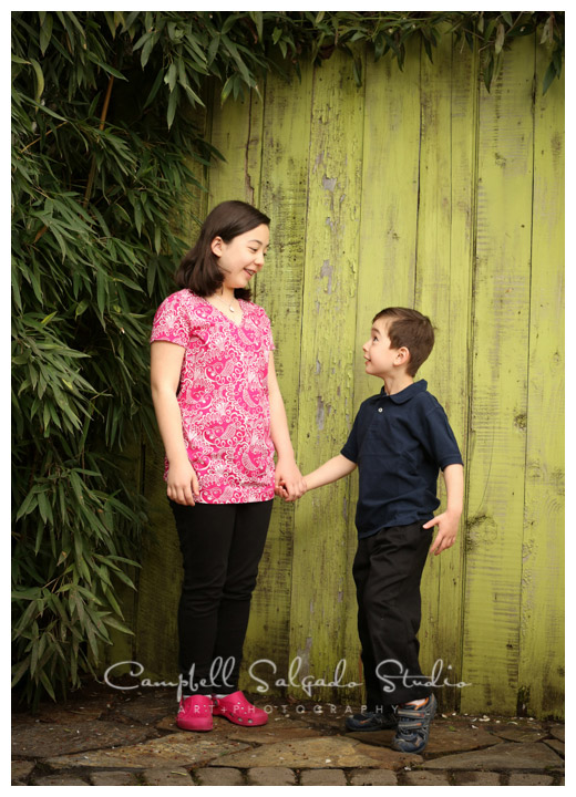 Portrait of siblings on green fence board background at Campbell Slagado studio,