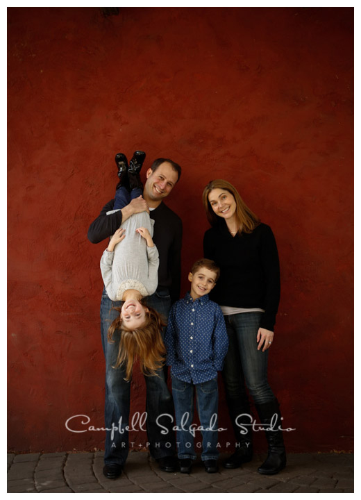 Portrait of family on red stucco background in Portland, Oregon at Campbell Salgado Studio.