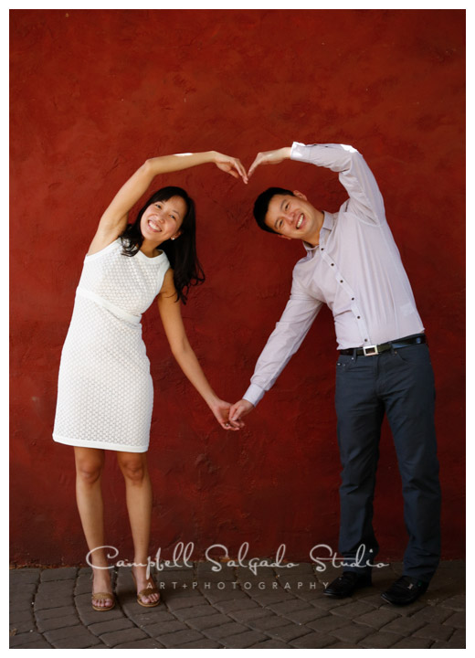 Portrait of couple on red stucco background in Portland, Oregon at Campbell Salgado Studio.