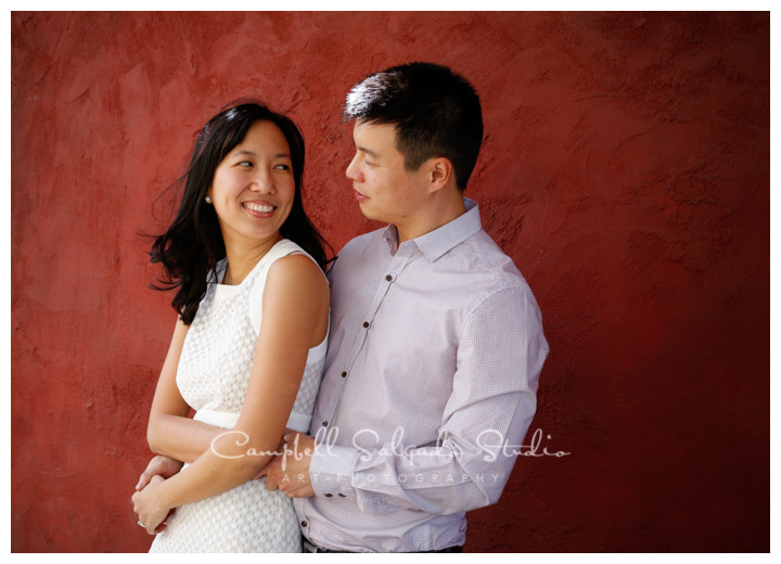Portrait of couple on red stucco background at Campbell Salgado Studio.