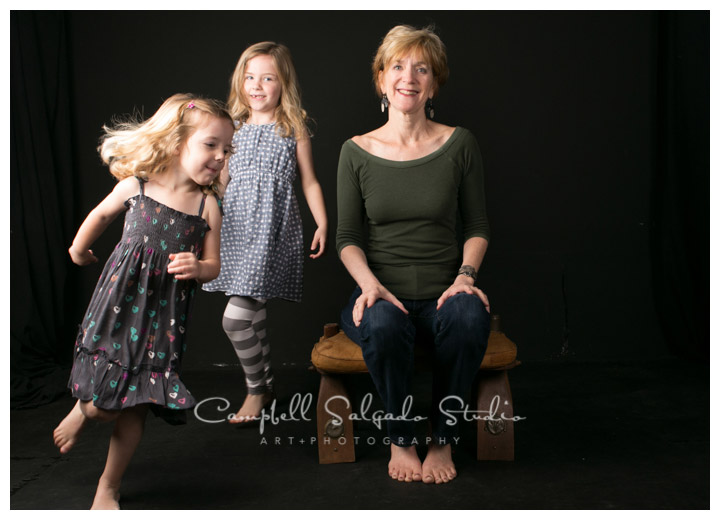 Portrait of granddaughters dancing around grandmother at Campbell Salgado Studio on black background.