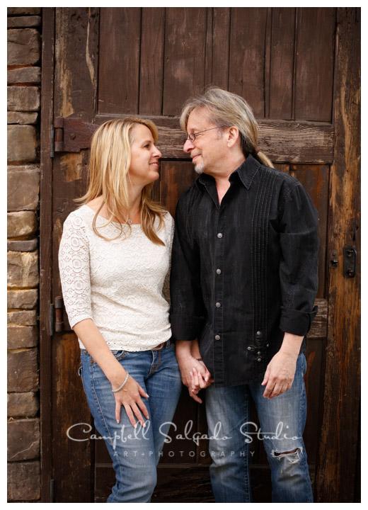 Portrait of couple on rustic door at Campbell Salgado Studio.