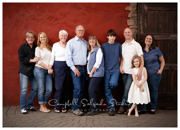 Portrait of extended family on red stucco background at Campbell Salgado Studio.
