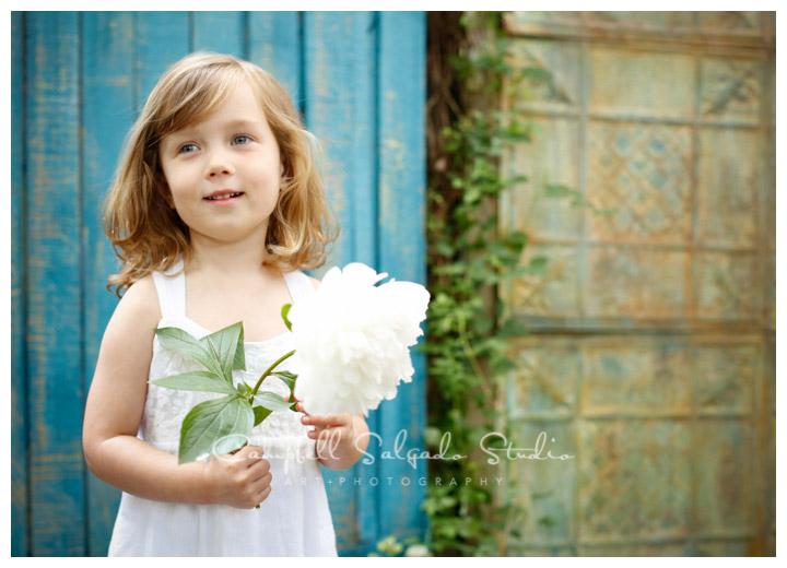 Portrait of child on blue fence board background at Campbell Salgado Studio.