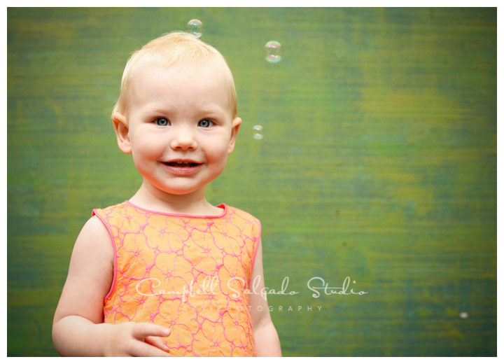Portrait of girl with bubbles on green weave background at Campbell Salgado Studio.