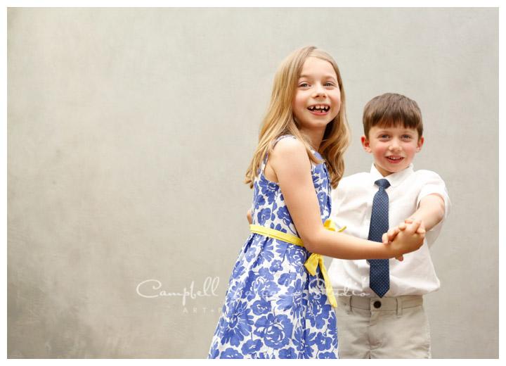 Portrait of siblings dancing on modern grey background at Campbell Salgado Studio.