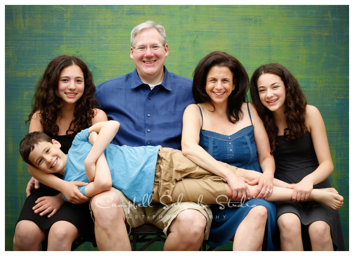 Portrait of family on green weave background at Campbell Salgado Studio.