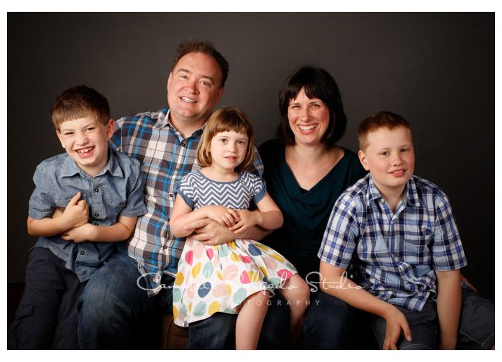 Portrait of family on grey background at Campbell Salgado Studio.