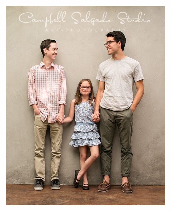 Children's photographers at Campbell Salgado Studio capture three siblings holding hands.