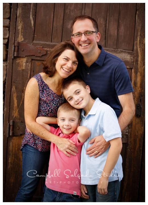 Portrait of family on rustic door background at Campbell Salgado Studio.