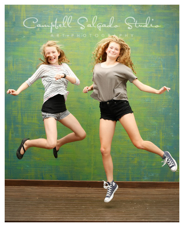 Sisters jumping in front of a green background for child photographer Kim Campbell with Campbell Salgado Studio.