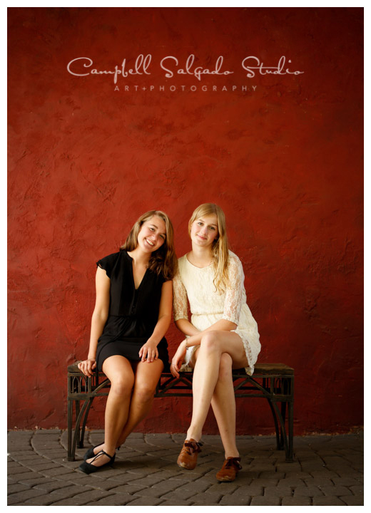 Portrait of sisters on red stucco background at Campbell Salgado Studio.