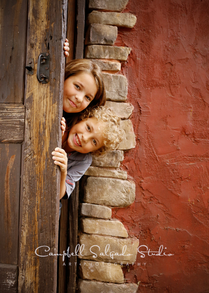 Portrait of children on rustic door background by family photographers at Campbell Salgado Studio, Portland, Oregon.