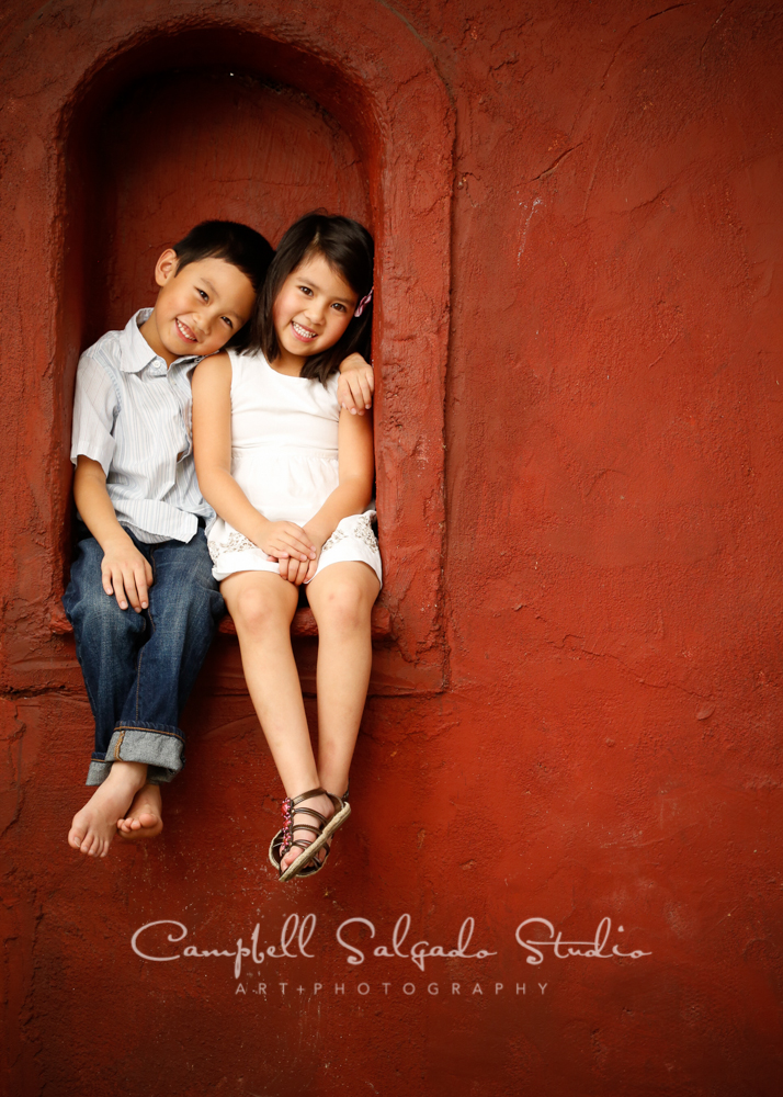 Portrait of twins on red stucco background by childrens photographers at Campbell Salgado Studio, Portland, Oregon.
