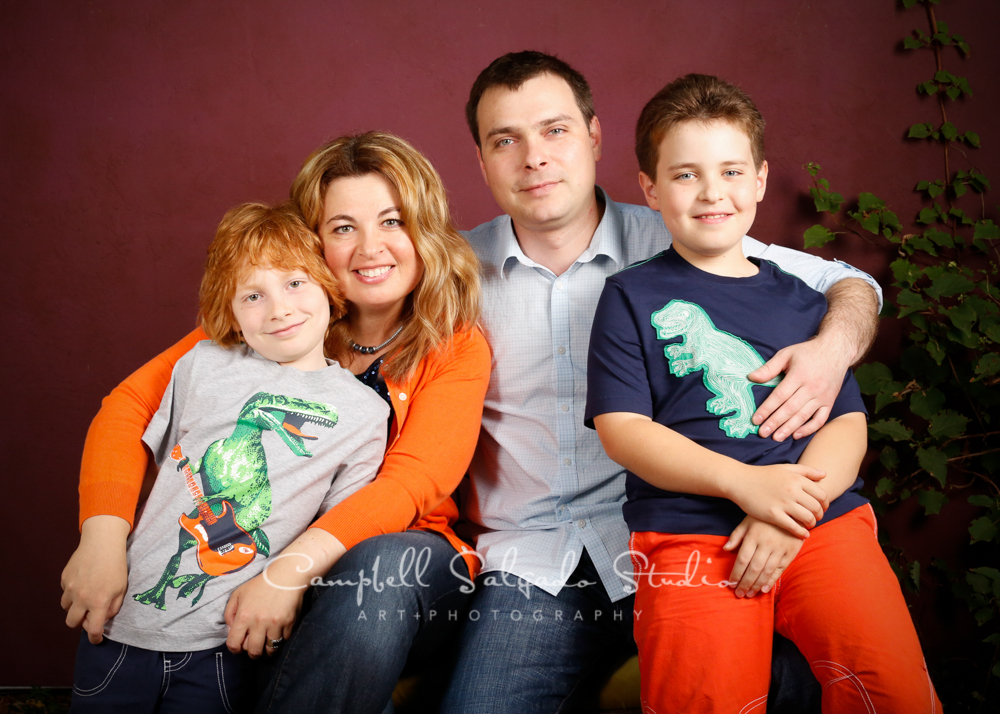 Portrait of family on plum stucco background by family photographers at Campbell Salgado Studio, Portland, Oregon.