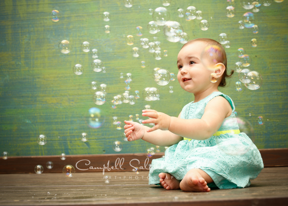 Portrait of baby girl on green weave background by child photographers at Campbell Salgado Studio, Portland, Oregon.