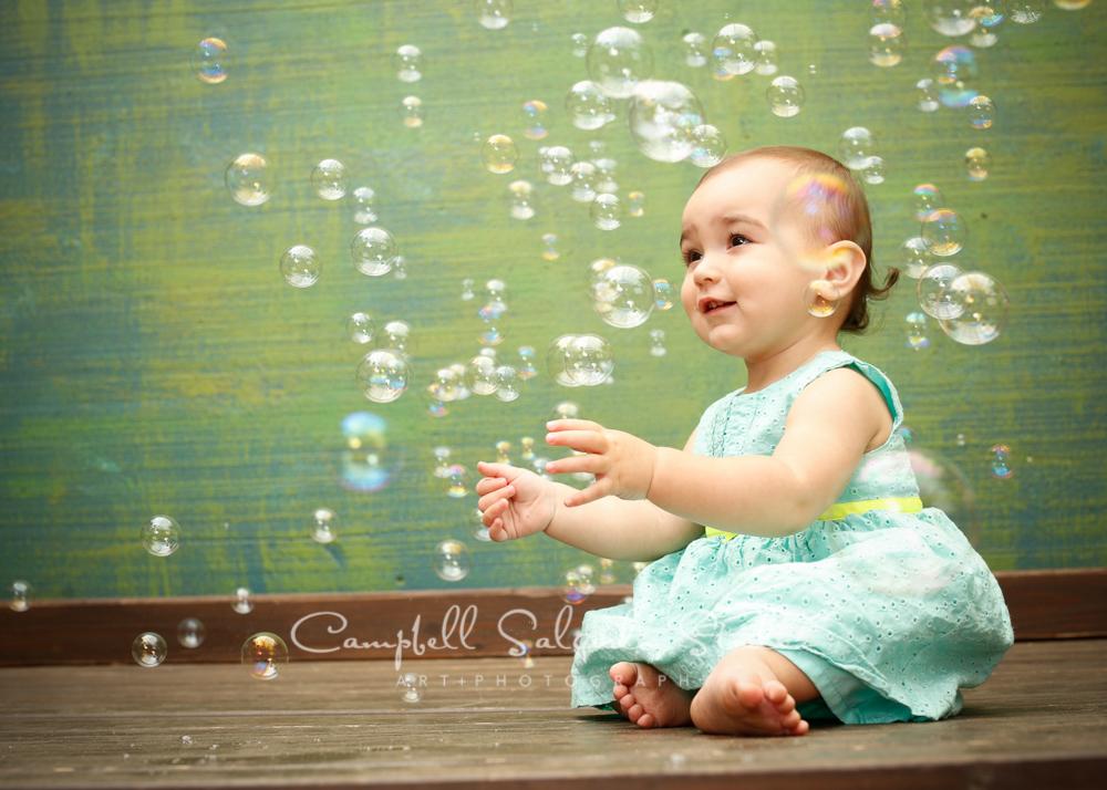 Portrait of baby girl on green weave backgroundby child photographers at Campbell Salgado Studio, Portland, Oregon.