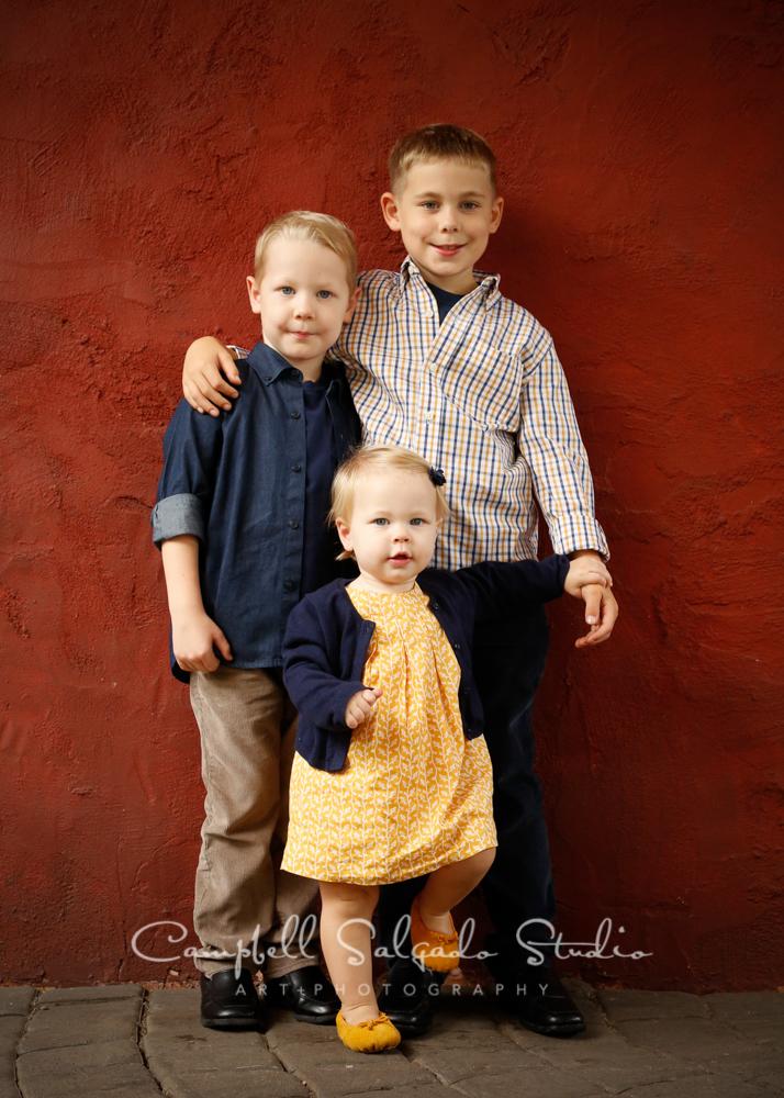 Portrait of children on red stucco backgroundby childrens photographers at Campbell Salgado Studio, Portland, Oregon.