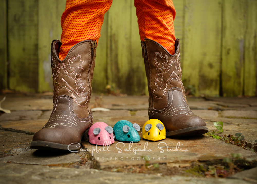 Portrait of girl in boots with toys on lime fence boards background by childrens photographers at Campbell Salgado Studio, Portland, Oregon.