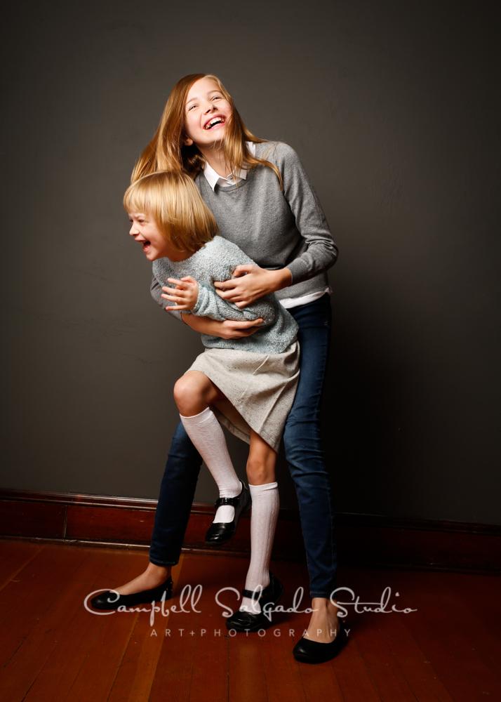 Portrait of sisters on grey backgroundby family photographers at Campbell Salgado Studio, Portland, Oregon.