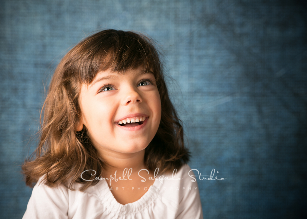 Portrait of girl on denim background by child photographers at Campbell Salgado Studio, Portland, Oregon.