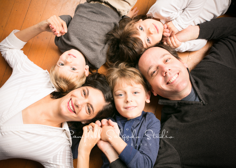 Portrait of family on pine floor by family photographers at Campbell Salgado Studio, Portland, Oregon.