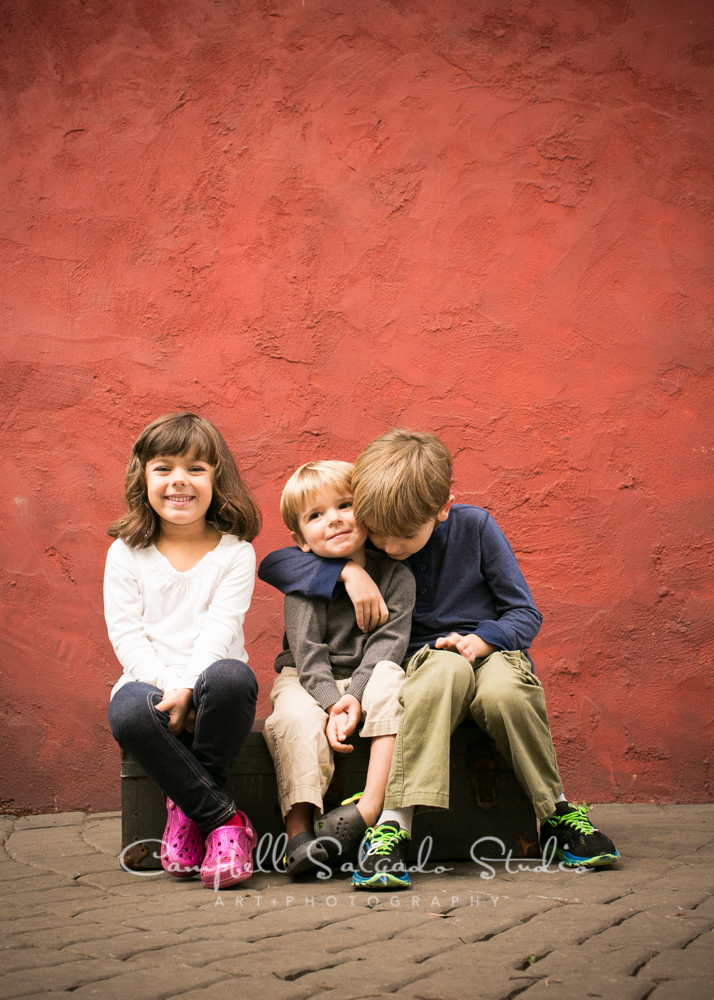 Portrait of children on red stucco background by children's photographers at Campbell Salgado Studio, Portland, Oregon.