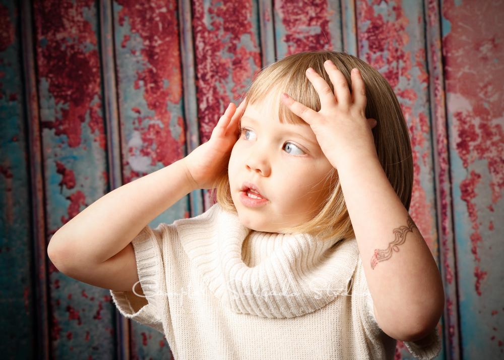 Portrait of girl on italian rust backgroundby child photographers at Campbell Salgado Studio, Portland, Oregon.