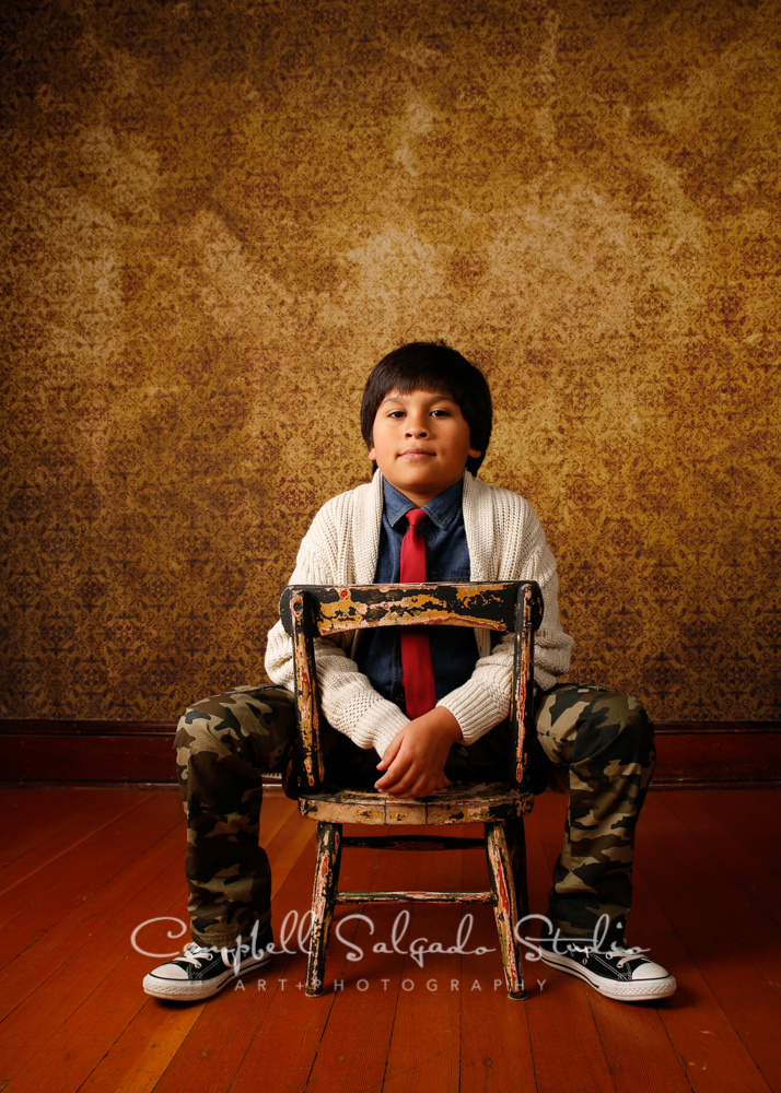 Portrait of boy on amber light background by child photographers at Campbell Salgado Studio, Portland, Oregon.