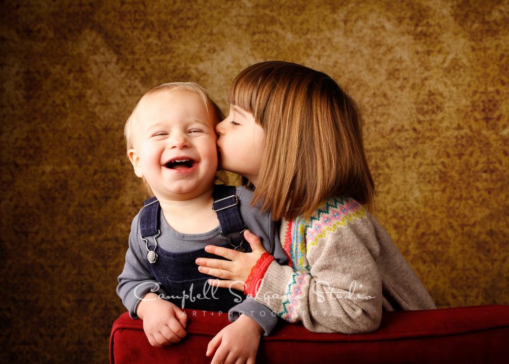 Portrait of siblings on amber light backgroundby child photographers at Campbell Salgado Studio, Portland, Oregon.