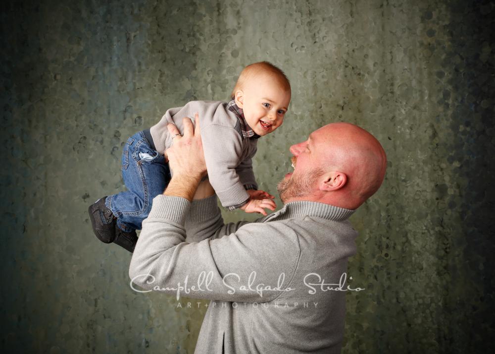 Portrait of father and son on rain dance backgroundby family photographers at Campbell Salgado Studio, Portland, Oregon.