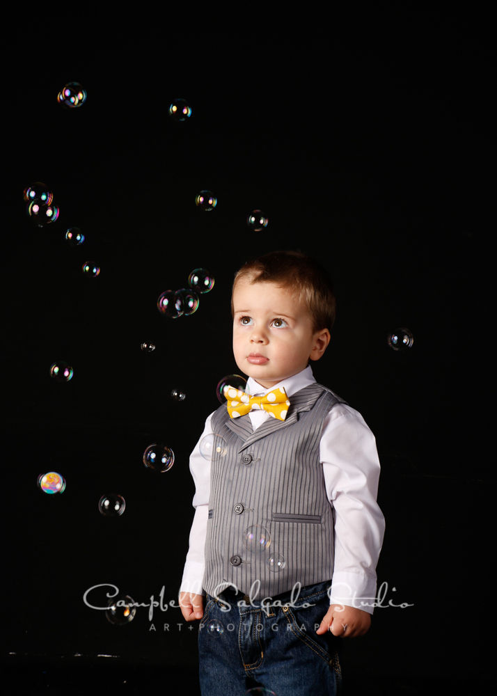 Portrait of child on black background with bubbles by child photographers at Campbell Salgado Studio, Portland, Oregon.