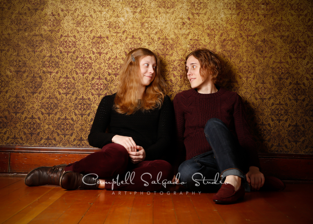 Portrait of sisters on amber light background by family photographers at Campbell Salgado Studio, Portland, Oregon.