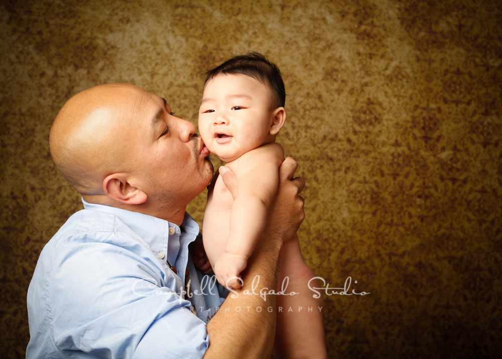 Portrait of father and son on amber light background by family photographers at Campbell Salgado Studio, Portland, Oregon.