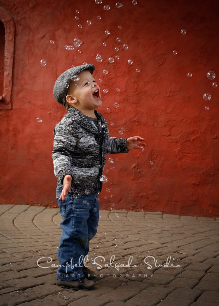 Portrait of child playing with bubbles on red stucco backgroundby child photographers at Campbell Salgado Studio, Portland, Oregon.