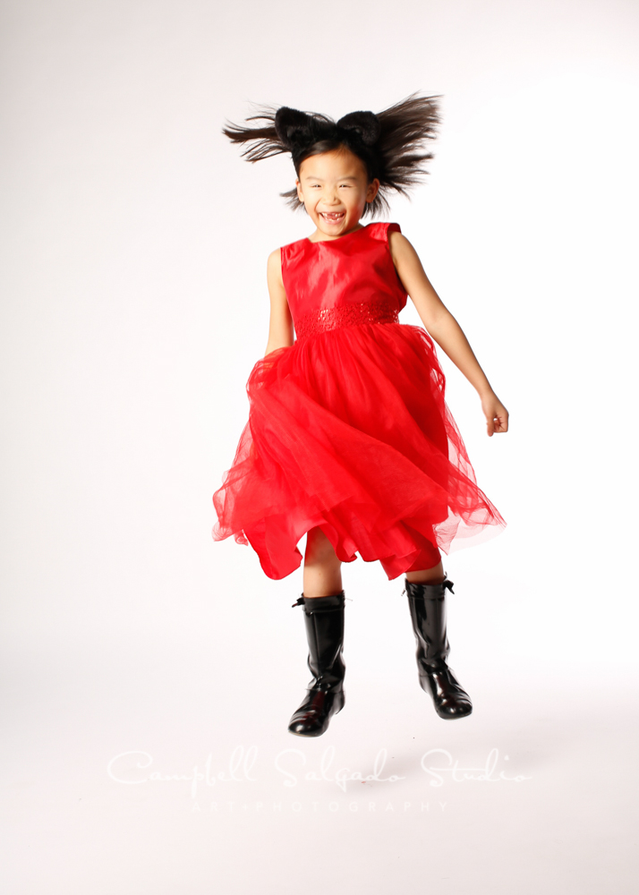 Portrait of girl in mid jump on white background by child photographers at Campbell Salgado Studio, Portland, Oregon.