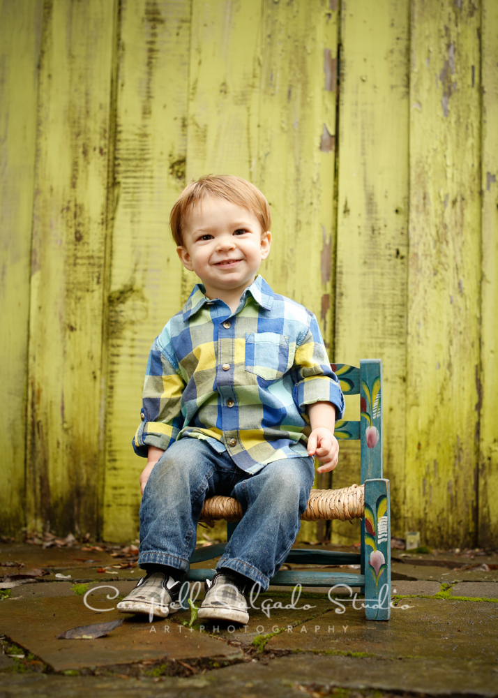 Portrait of boy in chair on lime fence boards background by child photographers at Campbell Salgado Studio, Portland, Oregon.