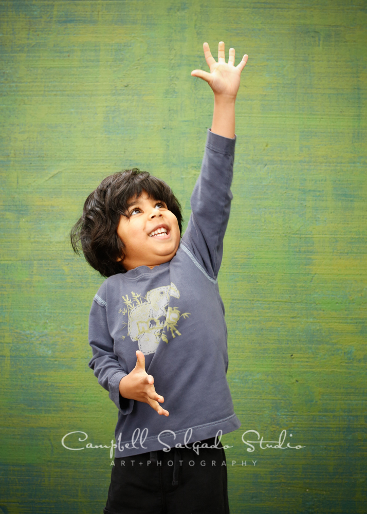 Portrait of child on blue-green weave background by child photographers at Campbell Salgado Studio, Portland, Oregon.