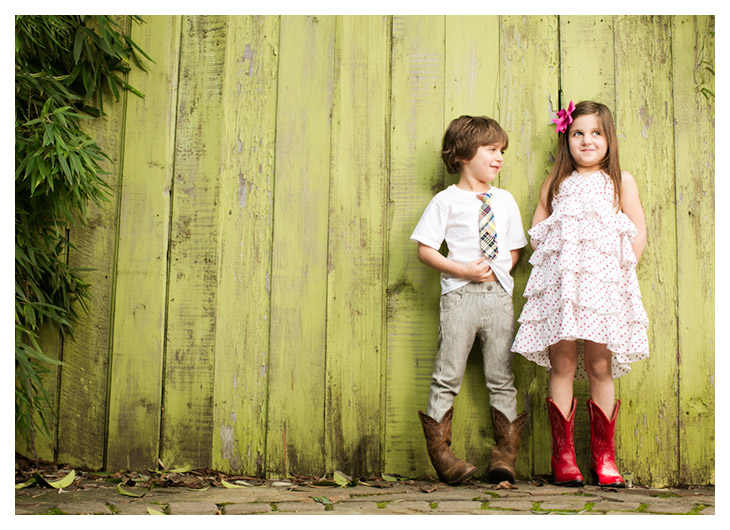 Child photographers at Campbell Salgado Studio in Portland Oregon capture a brother and sister in cowboy boots leaning against a green fence board wall.