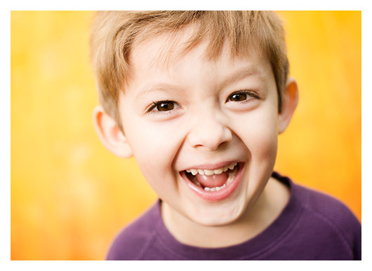 children's photographers at Campbell Salgado Studio in Portland Oregon photograph a young boy with a happy grin on his face against a yellow background.