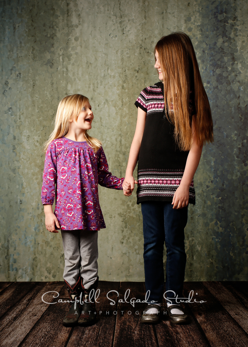 Portrait of sisters on rain dance backgroundby childrens photographers at Campbell Salgado Studio, Portland, Oregon.