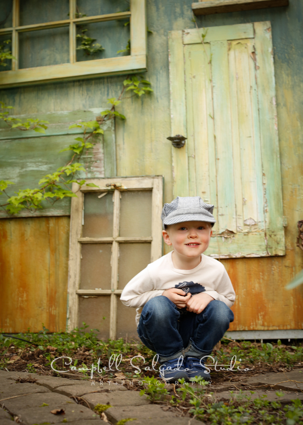 Portrait of child on vintage green doors background by childrens photographers at Campbell Salgado Studio, Portland, Oregon.