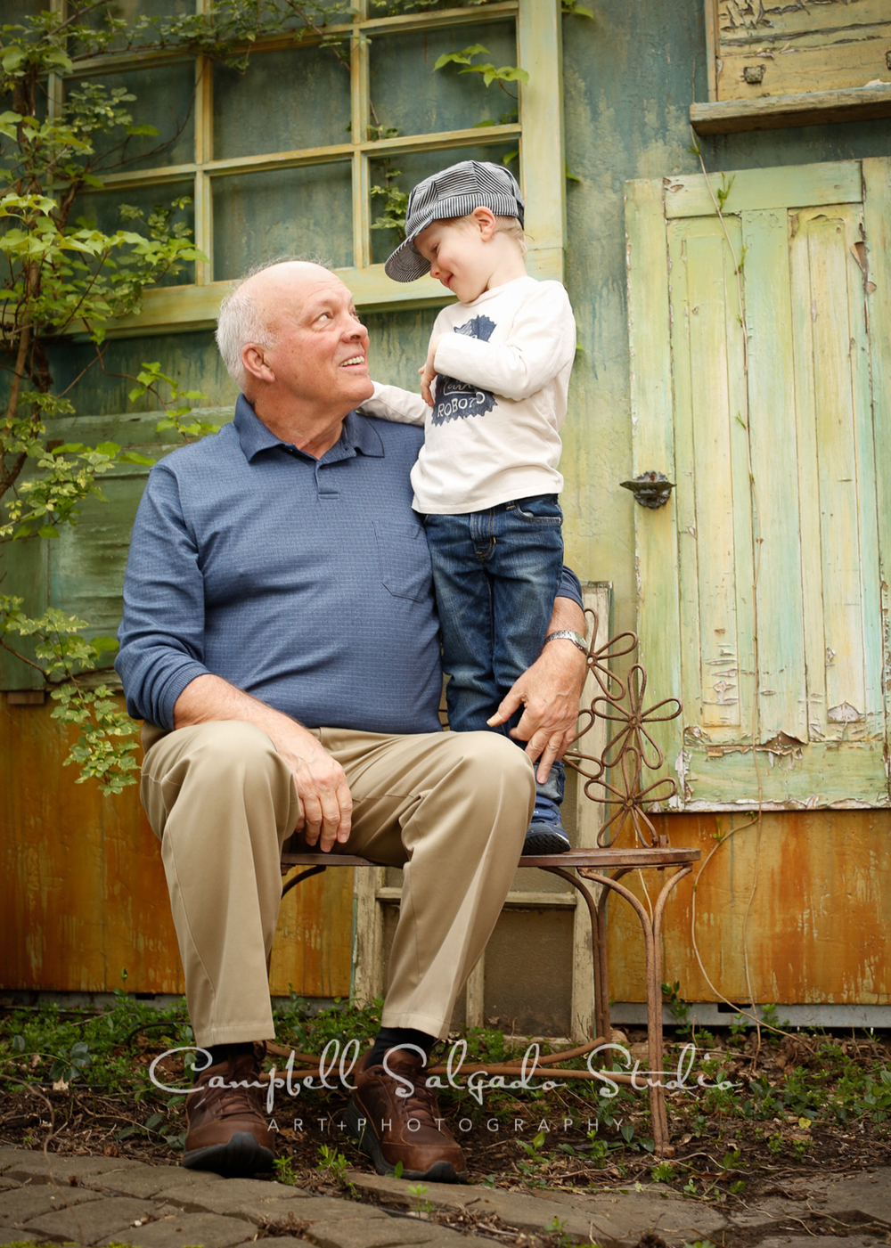 Portrait of child and grandfather on vintage green doors background by childrens photographers at Campbell Salgado Studio, Portland, Oregon.