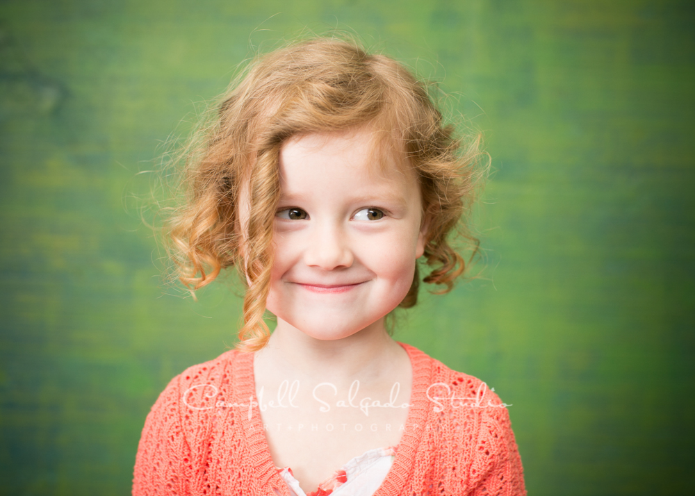 Portrait of girl on blue green weave background by child photographers at Campbell Salgado Studio, Portland, Oregon.