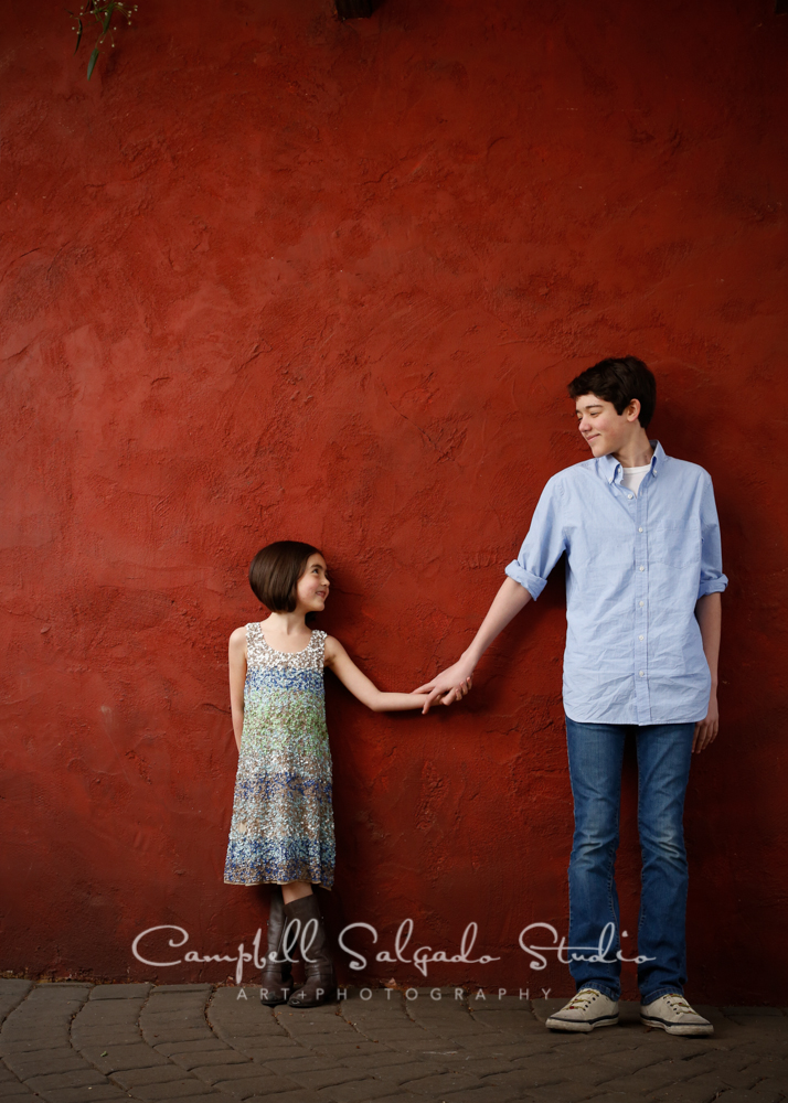 Portrait of children on red stucco background by family photographers at Campbell Salgado Studio, Portland, Oregon.
