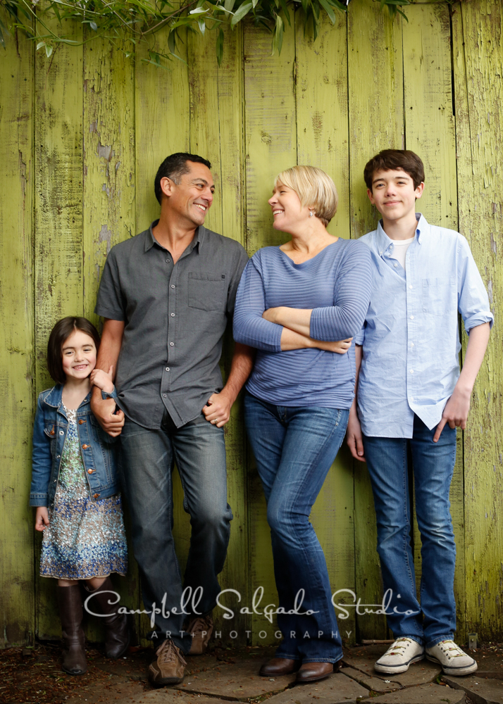 Portrait of family on green fence boards background by family photographers at Campbell Salgado Studio, Portland, Oregon.