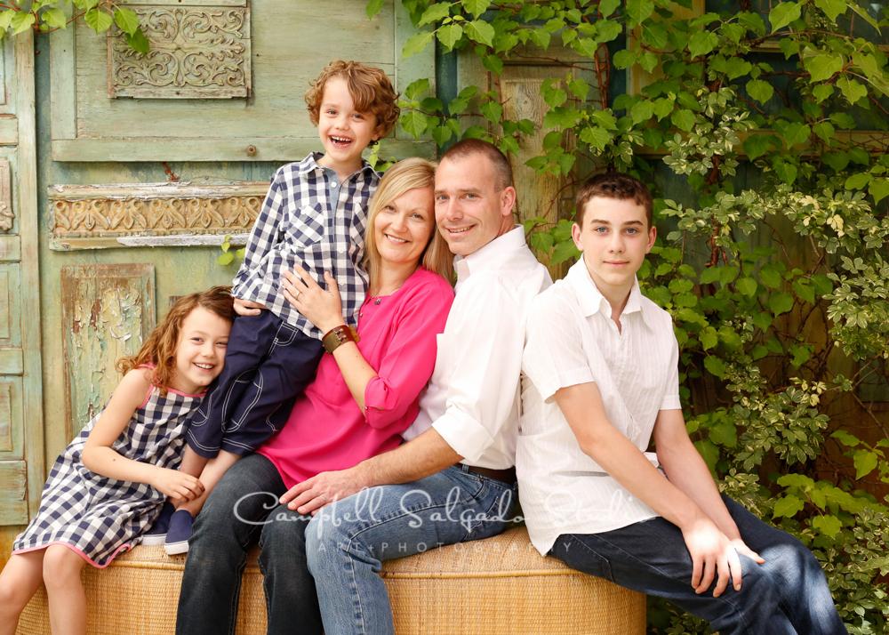 Portrait of family on vintage green doors backgroundby family photographers at Campbell Salgado Studio, Portland, Oregon.