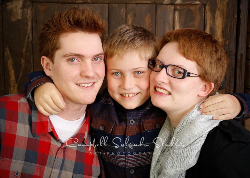 Portrait of siblings on rustic door backgroundby family photographers at Campbell Salgado Studio, Portland, Oregon.