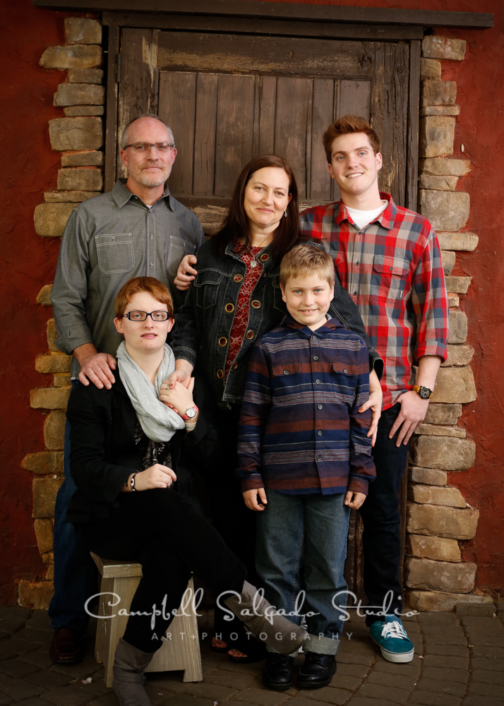 Portrait of family on rustic door background by family photographers at Campbell Salgado Studio, Portland, Oregon.