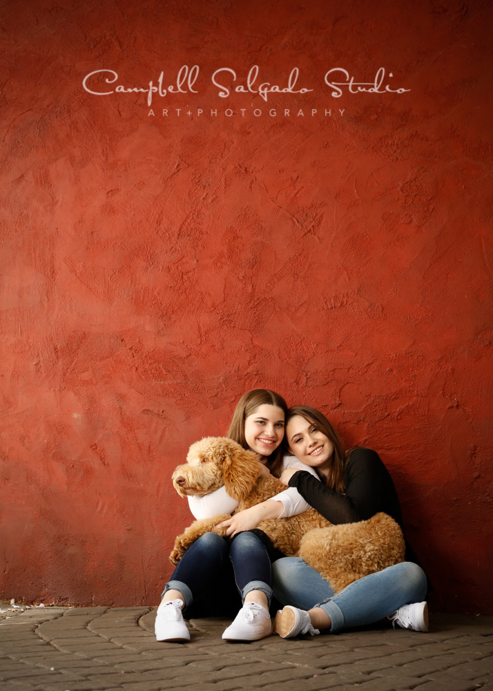 Portrait of sisters on red stucco background by child  photographers at Campbell Salgado Studio, Portland, Oregon.